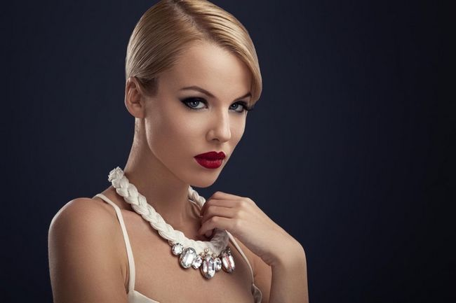 Beautiful blonde with red lipstick and the necklace around the neck posing in the studio