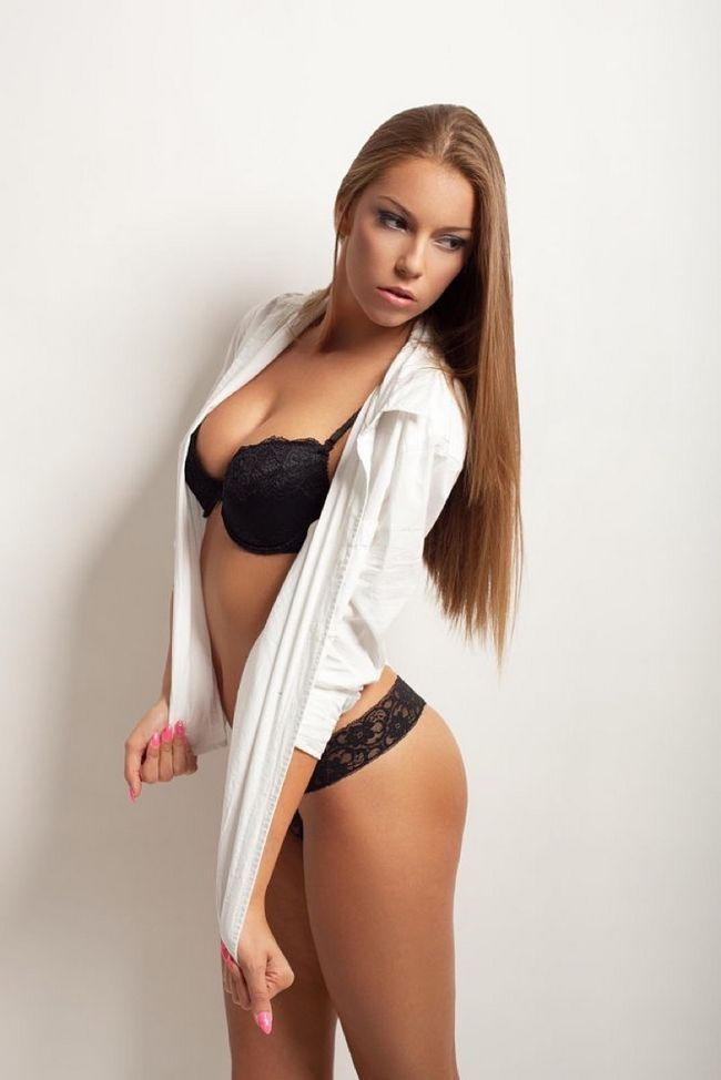 Beautiful young woman posing in lingerie and wearing a white men`s shirt