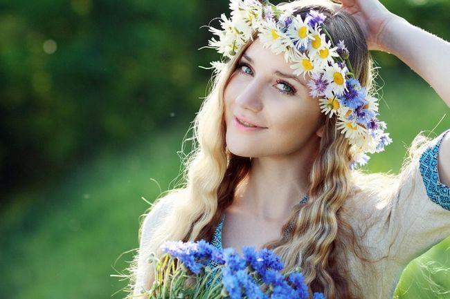 Beautiful ukrainian woman with flower wreath in fresh summer morning.
