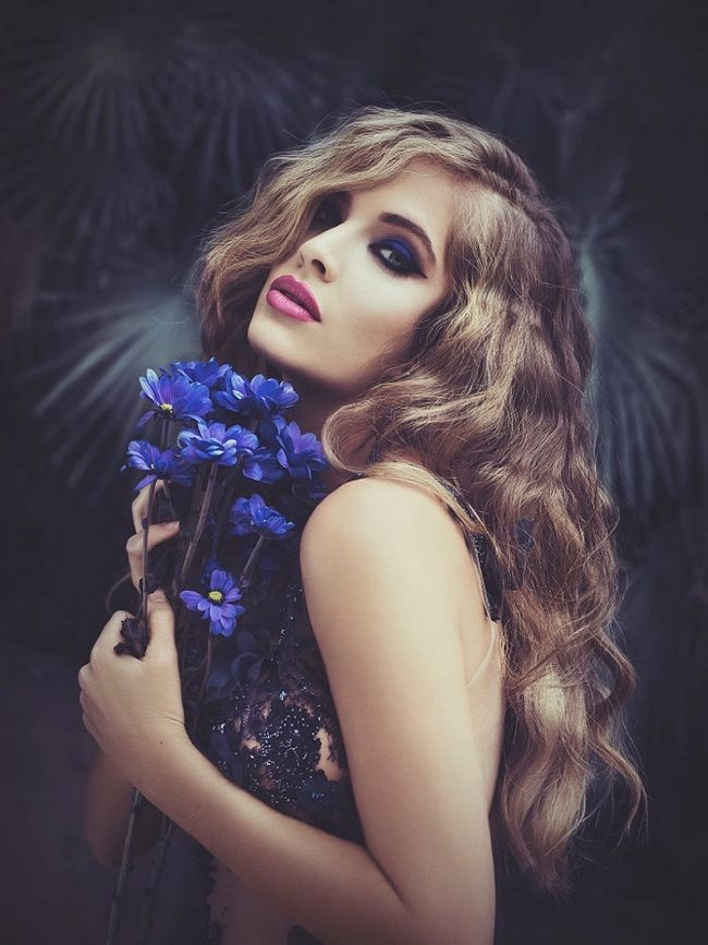 Blonde girl on natural light in exterior with blue flowers