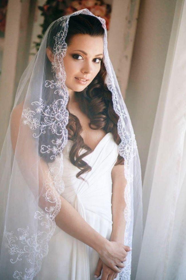 Выбор фаты также зависит от свадебной прически. Для распущенных волос, уложенных в аккуратные локоны, подойдет длинная модель фаты, а для высоких причесок,